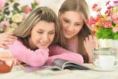 Rivista della lettura della figlia e della madre Immagini Stock Libere da Diritti