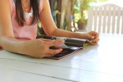 Rivista e lettura di apertura della mano della donna sulla tavola di legno a casa fotografia stock libera da diritti