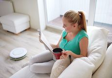 Rivista felice della lettura della donna con la tazza di tè a casa fotografia stock