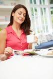 Rivista ispana della lettura della donna in cucina Fotografie Stock