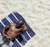 Rivista muscolare della lettura del giovane sulla spiaggia Fotografie Stock Libere da Diritti