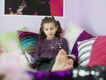 Rivista scalza della lettura della ragazza a letto Fotografia Stock