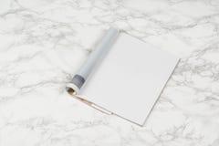 Riviste o catalogo del modello sul fondo di marmo bianco della tavola immagine stock