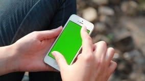 Rivne, Ucrânia - 28 de abril de 2015: Uma menina que usa o iphone com tela verde vídeos de arquivo