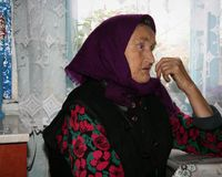 Woman. RIVNE, UKRAINE - 04 November 2008: Old Ukrainian woman with kerchief indoor Royalty Free Stock Photography