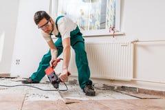 Rivning av gamla tegelplattor med tryckluftsborren Renovering av det gamla golvet royaltyfri fotografi