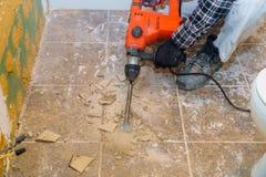 Rivning av gamla tegelplattor med tryckluftsborren Renovering av det gamla golvet royaltyfria bilder