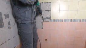 Rivning av gamla tegelplattor med tryckluftsborren Renovering av gamla väggar i badrummet eller köket stock video