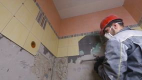 Rivning av gamla tegelplattor med tryckluftsborren Renovering av gamla väggar i badrummet eller köket arkivfilmer