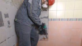Rivning av gamla tegelplattor med tryckluftsborren Renovering av gamla väggar i badrummet eller köket arkivfoto