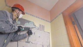 Rivning av gamla tegelplattor med tryckluftsborren Renovering av gamla väggar i badrummet eller köket arkivfoton