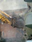 Rivning av hårdnar genom att använda en grävare Arkivbild