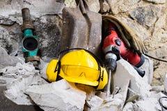 Rivning av väggar Hjälm för elektrisk hammare och utfrågningskydd som ligger på spillror Gammal tegelsten och omdanad byggande vä Arkivfoton