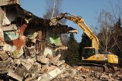Rivninggrävskopan förstör övergav byggnader i Milovice Arkivbilder