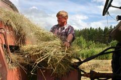 Rivolti il fieno il raccolto, trattore che raccoglie la pressa per balle del fieno, l'agricoltore fa usato la riparazione Fotografia Stock Libera da Diritti