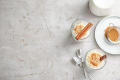 Riz au lait crémeux avec de la cannelle en verres servis sur la table grise, vue supérieure image libre de droits
