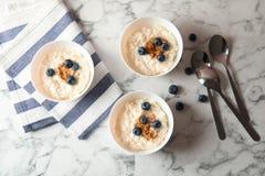 Riz au lait crémeux avec de la cannelle et des myrtilles dans des cuvettes servies sur la table de marbre photographie stock libre de droits