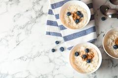 Riz au lait crémeux avec de la cannelle et des myrtilles dans des cuvettes servies sur la table de marbre, vue supérieure photo stock