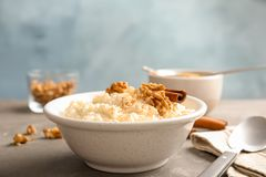 Riz au lait crémeux avec de la cannelle et des noix dans la cuvette servie sur la table photo libre de droits