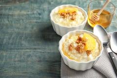 Riz au lait crémeux avec des noix et des tranches oranges en ramekins servis sur la table en bois images stock