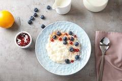 Riz au lait crémeux avec la groseille rouge et les myrtilles dans la cuvette servie sur la table grise, vue supérieure photos libres de droits