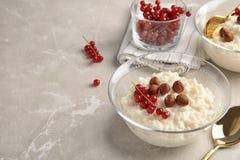 Riz au lait crémeux avec la groseille rouge et les noisettes dans des cuvettes servies sur la table grise photos libres de droits