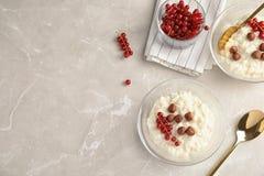 Riz au lait crémeux avec la groseille rouge et les noisettes dans des cuvettes servies sur la table grise, vue supérieure image stock
