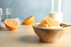 Riz au lait crémeux avec les tranches oranges dans la cuvette sur la table en bois photographie stock