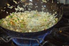 Riz avec des légumes et des oeufs dans une casserole asiatique de wok sur une cuisinière à gaz images stock