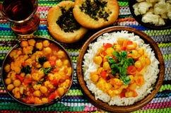 Riz avec des pois chiches de cari avec les légumes et le pain plat arabe Photographie stock