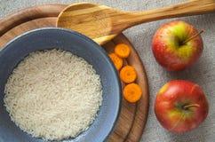 Riz avec des tranches de carotte sur un bureau en bois Image libre de droits
