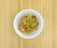 Riz avec le poulet et les légumes dans une cuvette blanche Photographie stock libre de droits