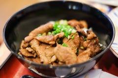 Riz avec le teriyaki grillé de porc et oignon de ressort sur le dessus au b image stock