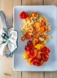 Riz blanc cuit, carottes et poivrons doux frits jaunes rouges d'un plat en céramique blanc sur une table en bois image stock