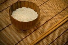 Riz blanc dans la cuvette sur le couvre-tapis en bois Photo libre de droits