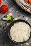 Riz blanc dans un plat noir sur un fond en bois, procédé de cuisson photo libre de droits
