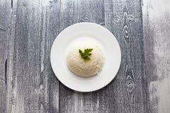 Riz bouilli dans un plat blanc Fond en bois Persil photos stock