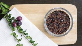 Riz brun cru avec les herbes et le raisin sur la configuration d'appartement de hachoir Photos libres de droits