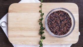 Riz brun et herbes crus sur le fla en bois de fond de hachoir Photo libre de droits
