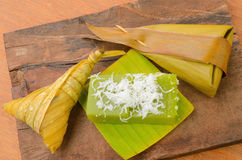 Riz collant de dessert thaïlandais enveloppé dans la feuille de banane sur le fond en bois images libres de droits