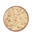 Riz cru dans la tasse en céramique sur le fond blanc Image stock