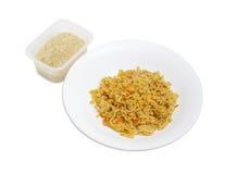 Riz cuit sur le plat et riz cru dans le récipient en plastique Photo libre de droits