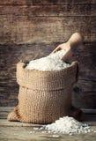 Riz dans le sac de toile de jute avec le scoop sur le fond en bois Photos stock