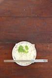 Riz de vapeur dans la cuvette blanche avec la baguette Image stock