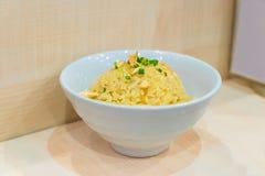Riz frit d'ail thaïlandais avec le légume sur le dessus dans la cuvette blanche, sur W Images stock