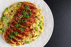 Riz frit d'oeufs de style chinois avec le filet découpé en tranches de porc Image stock