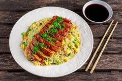 Riz frit d'oeufs de style chinois avec le filet découpé en tranches de porc sur la table en bois Images libres de droits