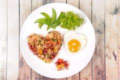 Riz frit de saucisse chinoise et oeuf ensoleillé dans des formes de coeur Images stock