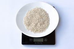 Riz italien cru dans un plat blanc sur une échelle noire de poids sur un fond blanc photo stock