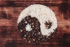 Riz noir et blanc formant un symbole de yang de yin Photo libre de droits
